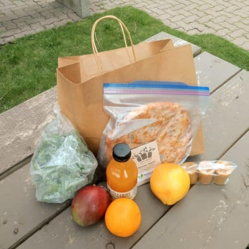 market items such as spinach, oranges, bread, and seeds on display with a bag on a picnic table