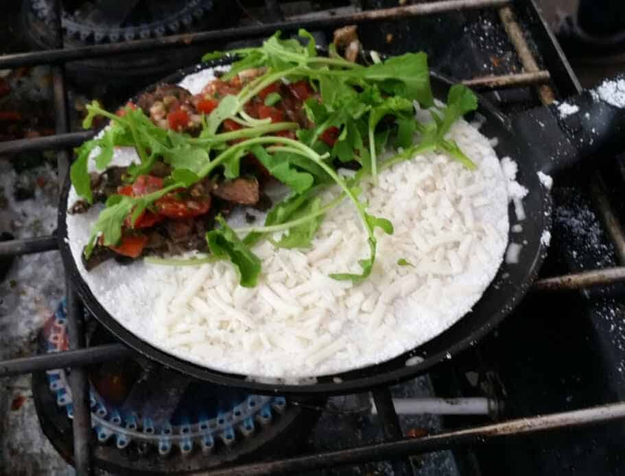 A tapioca crepe cooking in a thin pan with veggies and cheese
